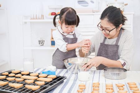 Pequeña muchacha asiática y su torta y galletas de la hornada de la madre en la cocina. Concepto de familia feliz y día de la madre