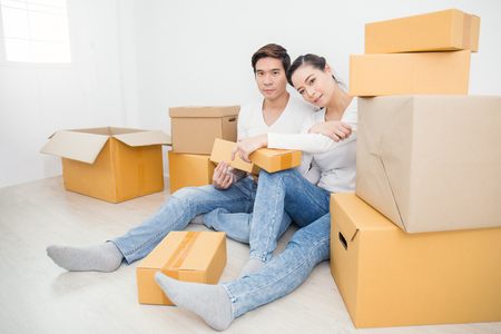 Asian woman and asian man carry boxes sitting on the floor with pile of boxes. Moving house just married asian couple concept. Stock Photo