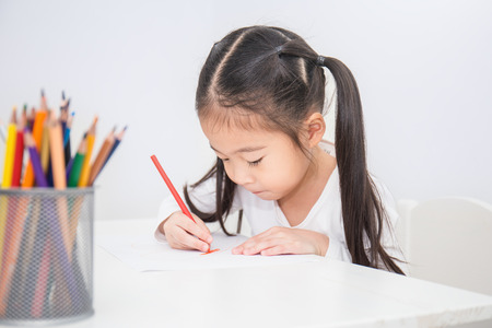 Education and school concept, little asian student girl drawing with pencils at school