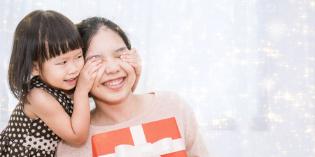 Little asian girl surprise her mother with gift box. Small asian girl toddler cover her mom eyes with her hands to surprise her with gift box. Boxing day holiday birthday christmas and mother's day concept.