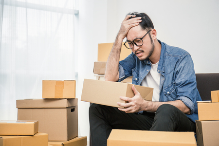 Start up small business entrepreneur SME or freelance asian man working with box at home concept, Young Asian small business owner, online marketing packaging box and delivery, SME bankrupt stress concept