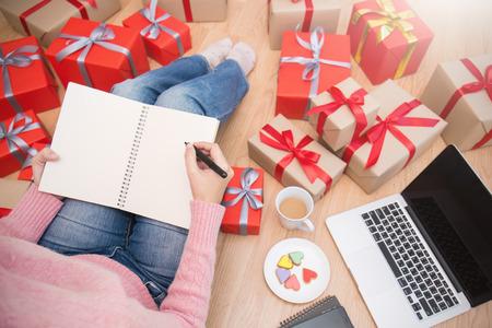 両手ペン ホワイティングをノートブックのクリスマス ギフト ボックス上面、祝うクリスマス ホリデー オンライン ショッピング背景バナーのコンセプトとの贈り物のリストを作るします。 写真素材 - 89708751