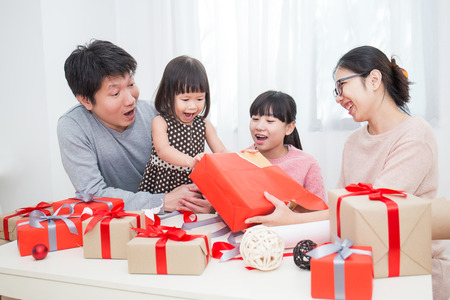 Asian family in sofa giving presents for Christmas, asian family celebrate Christmas boxing day open the gift