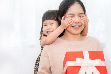 Little asian girl surprise her mother with gift box her hands cover her mother face. Boxing day holiday birthday christmas and mother's day concept.