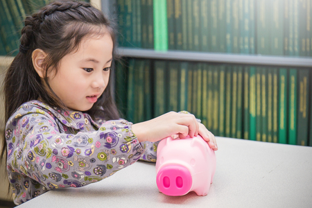 Portrait of little asian toddler girl putting money into piggy bank for future savings. Education investing and financial concept