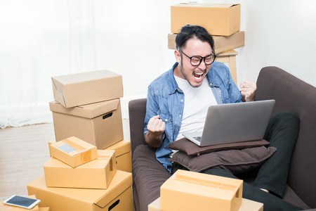 Start up small business entrepreneur SME or freelance asian man typing computer with box, Young happy success Asian man with his hand lift up , online marketing packaging box and delivery, SME concept   Stockfoto