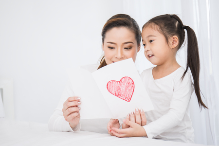 little aisan girl daughter congratulates mom and gives a heart postcard. Mum and girl smiling and hugging. Family holiday mother's day and togetherness concept.