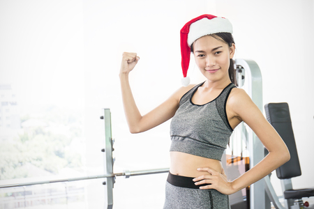 Portrait of Asian young beautiful woman wearing santa red hat posting in the gym, asian woman work out at the gym sport club celebrate Christmas party Banque d'images