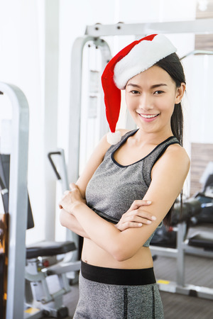 Portrait of Asian young beautiful tan woman  wearing santa red hat posting in the gym , asian woman work out  at the gym sport club celebrate Christmas  party Banque d'images