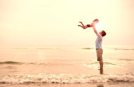Asiatischer Vater und kleines Mädchen, die auf dem Strand bei dem Sonnenuntergang, Vati hält Tochterfliegen am Strand spielt. Gemeinsam lieben Familienkonzept. Vatertag