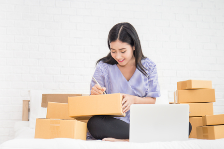Start up small business entrepreneur SME or freelance asian woman working with box at home concept, Young Asian small business owner, online marketing packaging box and delivery, SME concept Standard-Bild
