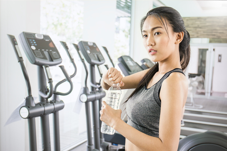 Asian young woman drinking water after exercise, asian athlete drinking a bottle of water at the sport club gym. Asian tan skin color woman holding a bottle of water. Stock Photo