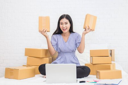 Start up small business entrepreneur SME or freelance woman holding boxes working at home concept, Young Asian small business owner at home office, on line marketing packaging and delivery, SME concept