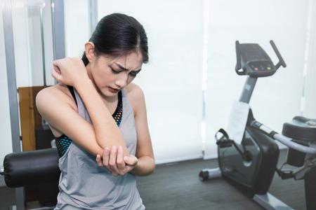 Junge schöne asiatische Frau, die die Schmerz in ihrem Arm und in Ellbogen, asiatische Frau mit zwei Händen berühren ihren Ellbogen, schmerzlichen Unfall vom Sportgesundheitswesen und medizinisches Konzept hat