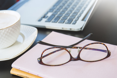 close up eye glasses books and laptop on the table, coffee break office hour concept