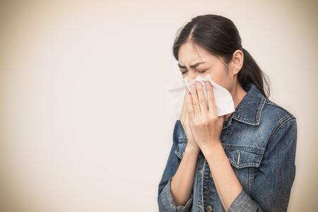 Mujer con un resfriado que sopla su nariz que moquea con el tejido. Retrato de muchacha hermosa asiática enferma estornudos de gripe. Concepto sanitario y médico.