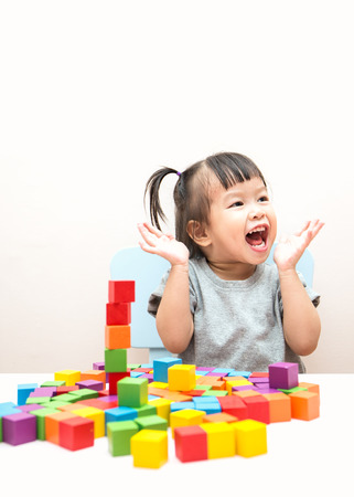 Little toddler asian girl playing blocks on the table. Stack of colorful wooden blocks on a white background. Learning by doing education concept.