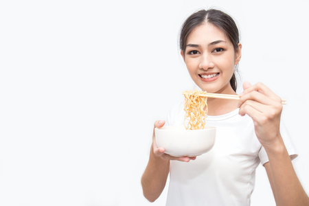 Young beautiful asian woman eating yummy hot and spicy instant noodle using chopsticks isolated on white background. Asian girl servile end of the month with cheap food.