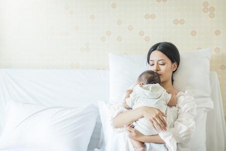 Bouchent le portrait de la belle jeune mère asiatique avec bébé nouveau-né, espace copie avec lit à l'hôpital. Concept de jour de mère de style de vie de soins de santé et d'amour médical Banque d'images