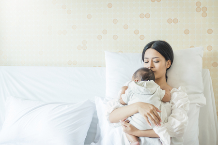 Ciérrese encima del retrato de la madre asiática joven hermosa con el bebé recién nacido, copie el espacio con la cama en el hospital. Concepto de día de la madre de estilo de vida de amor médico y sanitario Foto de archivo