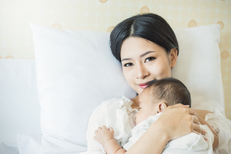 Close up portrait of beautiful young asian mother with her newborn baby, copy space with bed in the hospital background. Healthcare and medical love, lifestyle concept Standard-Bild