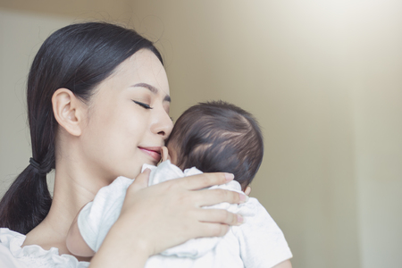 Close up portrait of beautiful young asian mother kissing her newborn baby. Healthcare and medical love lifestyle mother's day concept