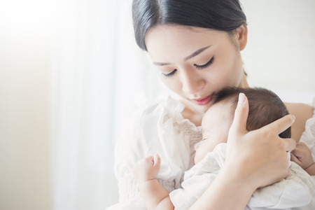 Close up portrait of beautiful young asian mother with her newborn baby, copy space with bed in the hospital background. Healthcare and medical love, lifestyle mother's day concept Foto de archivo