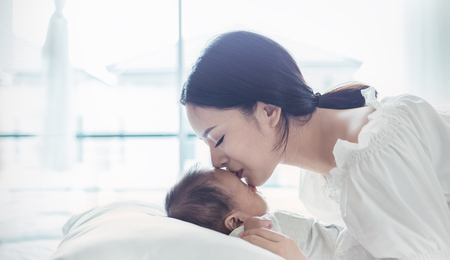 Close up portrait of beautiful young asian mother kissing her newborn baby. Healthcare and medical love lifestyle mother's day concept banner