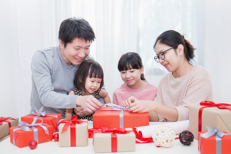 Asian little girl help her father and mother  wrapping gift box, celebration holiday christmas mother's day concept. Happy asian family unwrap gift boxed together. Stockfoto