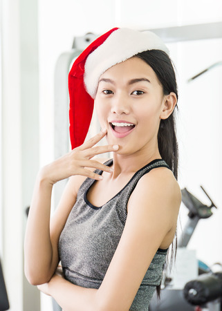 Portrait of Asian young beautiful woman wearing santa red hat posting in the gym, asian woman work out at the gym sport club celebrate surprise Christmas party Banque d'images