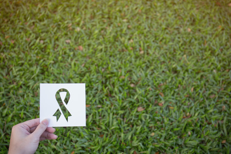 Hands holding cut paper with logo of ribbon over green glass background. Symbol for breast cancer awareness Stock Photo