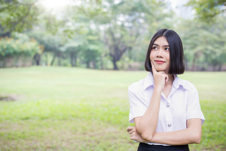 Portrait of asian woman smile and look up with copy space. Happy asian beautiful teenage girl having good time in the park. Education back to school spring summer concept. 写真素材