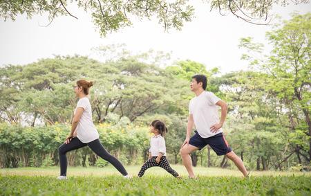 Familia haciendo ejercicio y trotando juntos en el parque. Grupo de padre de familia, madre e hija que se extiende después del deporte en la hierba. Concepto médico y de salud deportiva.