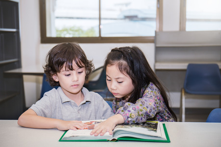 Two young children boy and girl reading books at the school library, Education group study concept