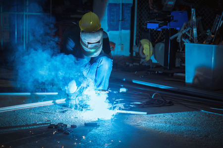 Worker while doing a welding with arc welder with the smoke, asian man wearing mask with his hands welding in heavy industry 免版税图像