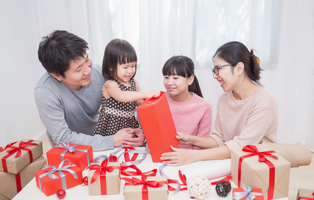 Asian little girl help her mother and father wrapping gift box, celebration holiday christmas mother's day concept. Happy asian family in Christmas season Stockfoto