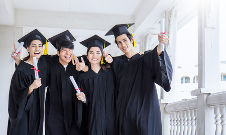 Young asian man and woman graduates holding certificate standing in line in front of university building on graduation day. Success team work achievement celebration concept and banner.