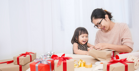 Asian little girl help her mother wrapping gift box, celebration holiday christmas mother's day concept.