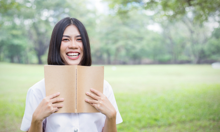 Portrait of asian woman holding book. Happy asian beautiful teenage girl laughing with notebook in hands in the park. Education success back to school spring summer concept.