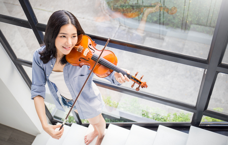 Portrait of beautiful young asian woman playing violin. Education leisure and recreation concept Stock Photo
