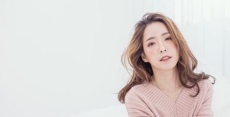 Retrato de joven bella mujer asiática relajarse en su dormitorio. Sonrisa feliz adolescente asiática aislada en banner de fondo blanco.