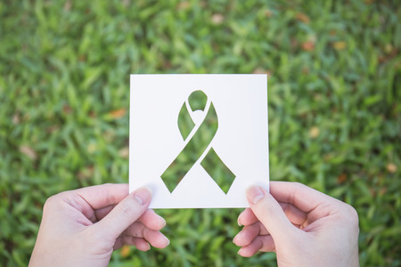 Hands holding cut paper with logo of ribbon over green glass background. Symbol for breast cancer awareness. Healthcare and medical spring concept Foto de archivo