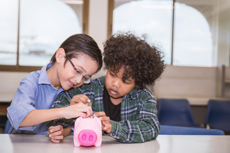 Little boys putting money into piggy bank for future savings, Friendship education financial learning concept