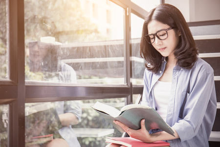 Portrait of attractive asian student ( woman ) holding cup of coffee reading a book near the window. Lifestyle relax education exam preparing concept. Vintage morning light