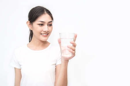 Close up portrait of beautiful asian woman drinking glass of water isolated on white background. Healthy healthcare lifestyle and medical concept