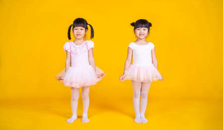Portrait of two little asian child girl dreams of becoming ballerina in a pink tutu skirt isolated on yellow background. Happy young girl practise her dance. Education childhood toddler lifestyle concept