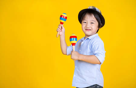 Portrait of little cute asian boy playing the maracas isolated on yellow background, preschool play group, music learning by doing and education concept