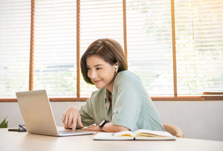 Portrait of happy young asian girl student wear headphone watch webinar conference video call. Young woman listen online course communicate, e-learn language lesson looking at laptop at home. Virtual concept Zdjęcie Seryjne