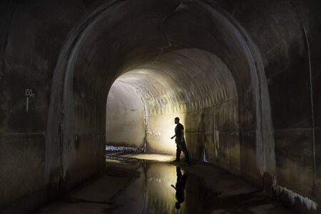 culvert: Man stood in large arched tunnel