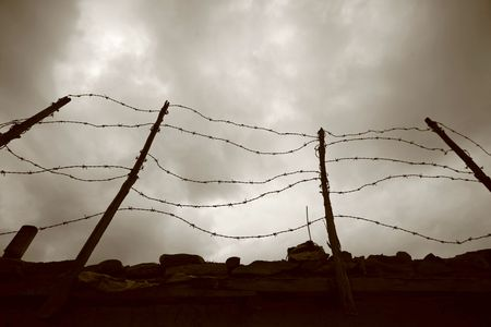 condemned: barbed wire fence and wall Stock Photo
